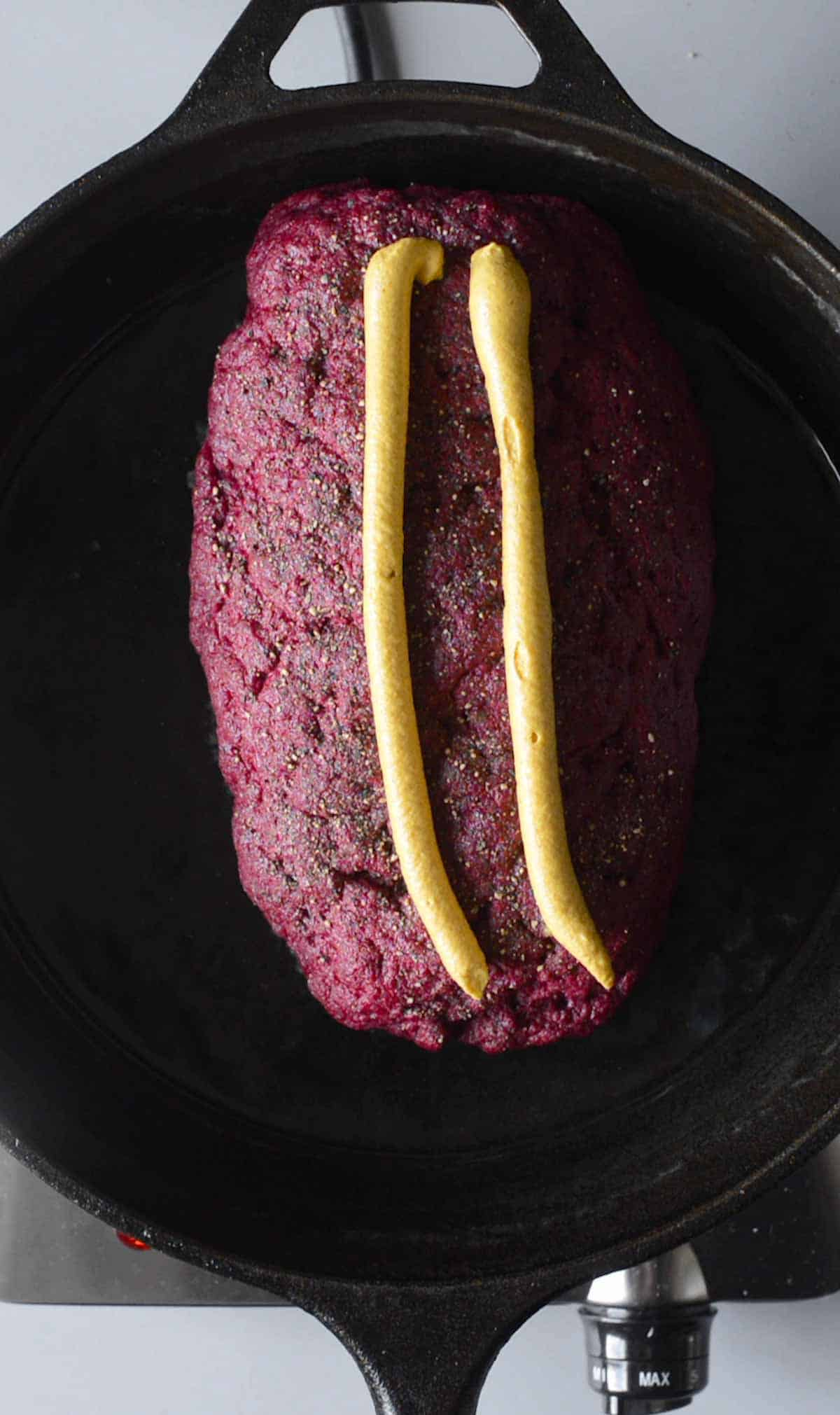 roast beef in a pan, covered with mustard