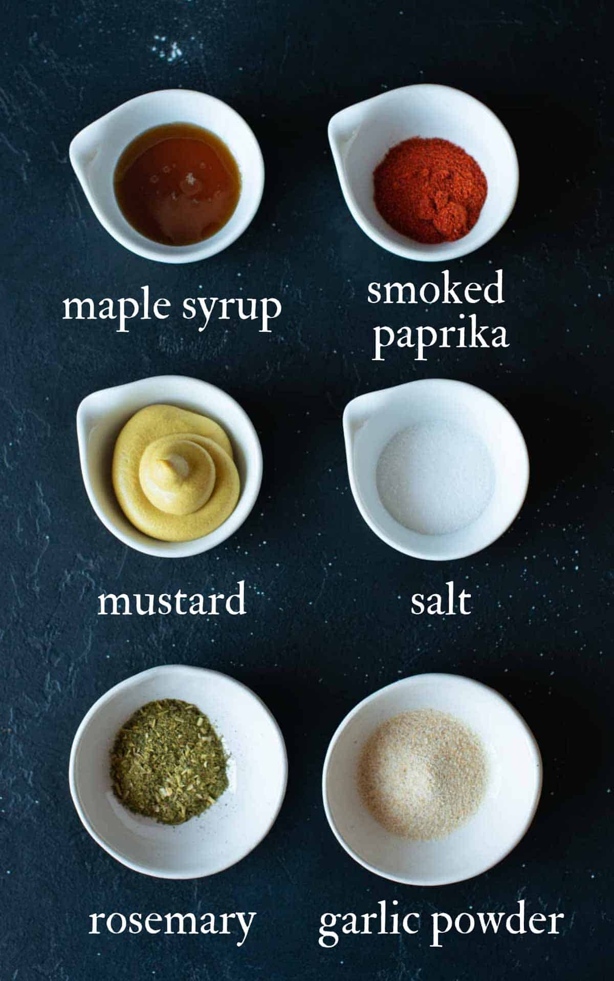 picture showing all the spices used in the recipe: maple syrup, paprika, mustard, salt, rosemary and garlic powder